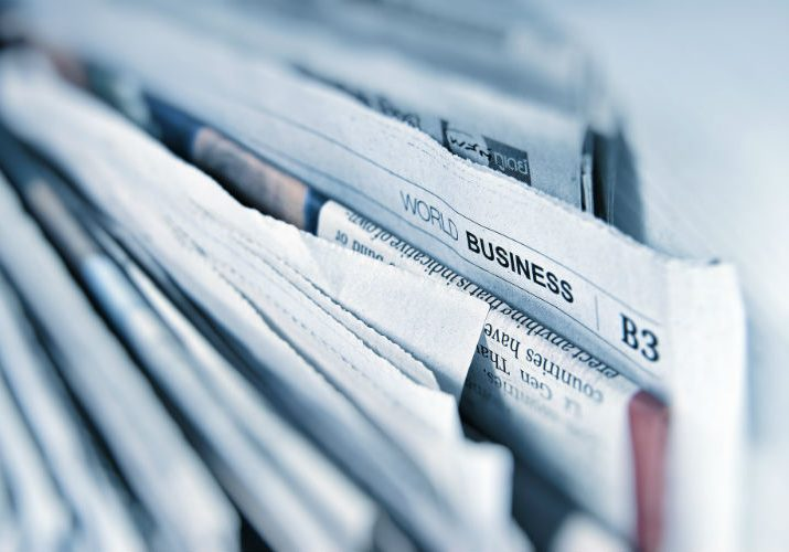 A photo of a stack of newspapers representing the news section of the website
